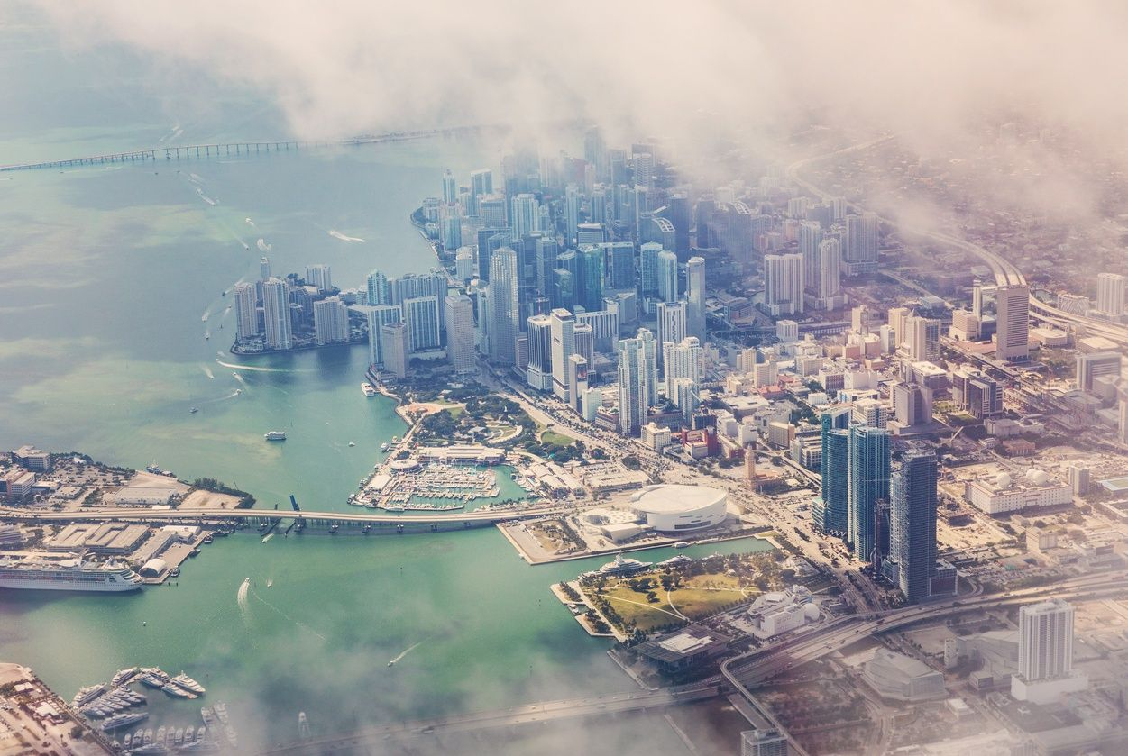 an aerial view of downtown miami through the clouds