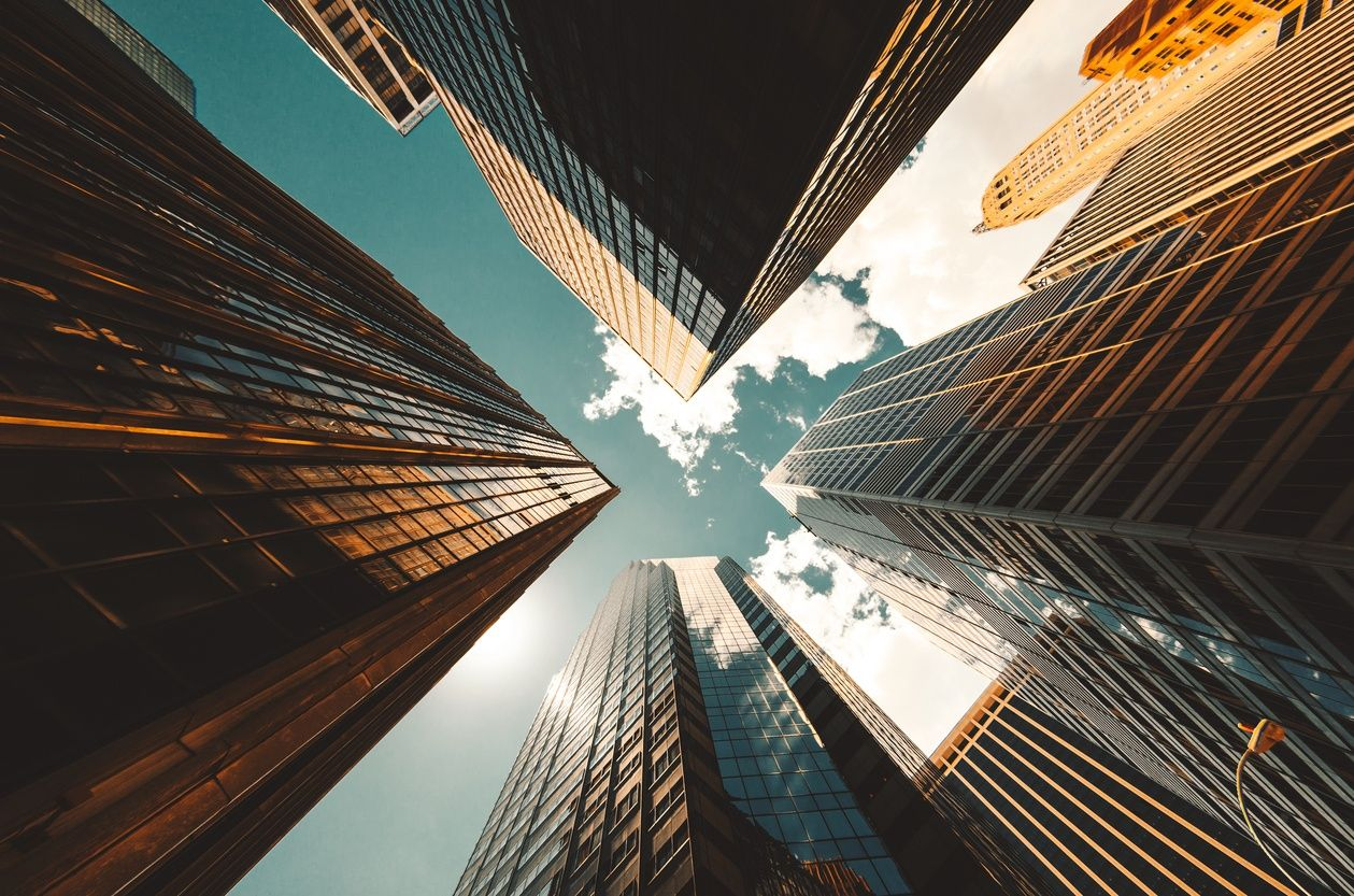picture looking up at the sky through a number of New York City skyscrapers