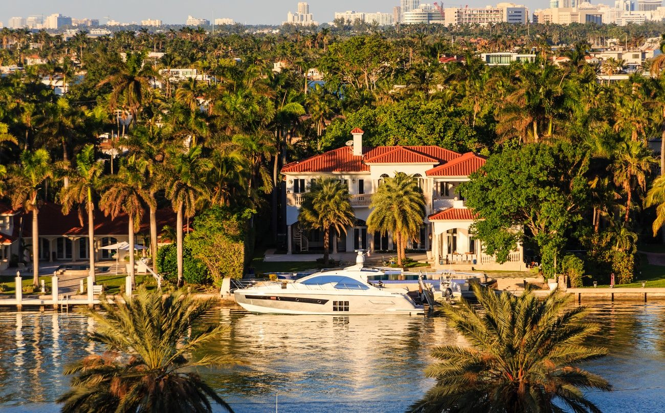 a waterfront miami mansion with a white yacht also pictured